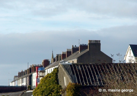 Chimneys with pots atop row houses in Caernarfon