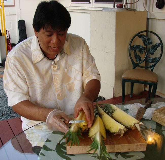 Rance Villarimo demonstrates how to cut pineapple at Tutu's Place, Maui, Hawaii