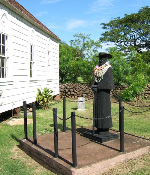 Statue of Father Damien alongside St. Joseph's Church is adorned with floral garlands Molokai Hawaii